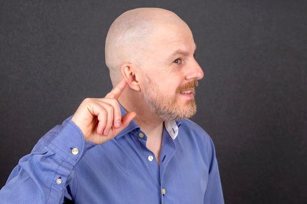 あごひげを生やした男は彼の耳に彼の指を向けます