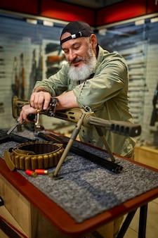 ひげを生やした男が銃店の強力なライフルでポーズをとる。武器屋のインテリア、弾薬と弾薬の品揃え、銃の選択、射撃の趣味とライフスタイル、護身術
