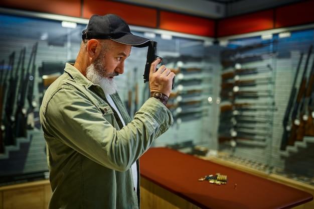 ひげを生やした男は銃の店で黒いピストルでポーズをとる。武器屋のインテリア、弾薬と弾薬の品揃え、銃器の選択、射撃の趣味とライフスタイル、護身術