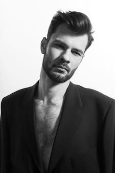 Bearded man posing in black suit, with naked torso