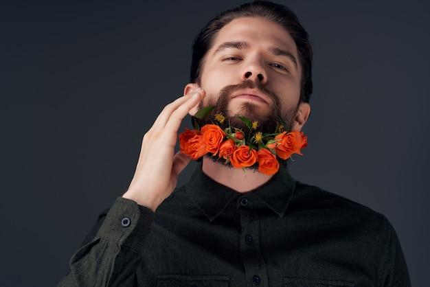 ひげを生やした男がひげのファッションのクローズアップで花をポーズ