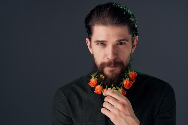 ひげを生やした男は、ひげのファッションの孤立した背景で花をポーズ