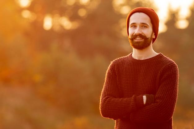 Бородатый мужчина позирует на природе с копией пространства