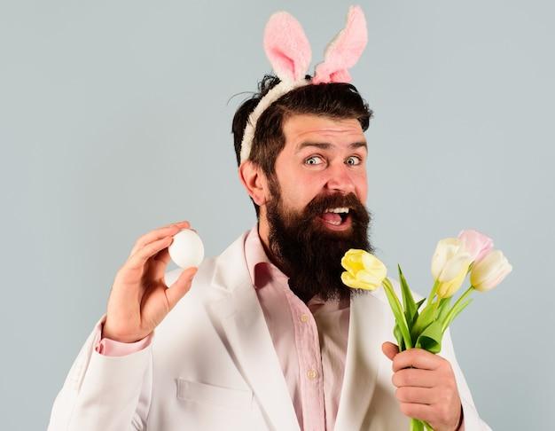 Бородатый мужчина готовится к пасхе. охота на яйца. человек-кролик. улыбающийся бородатый мужчина в костюме с яйцом и цветами.