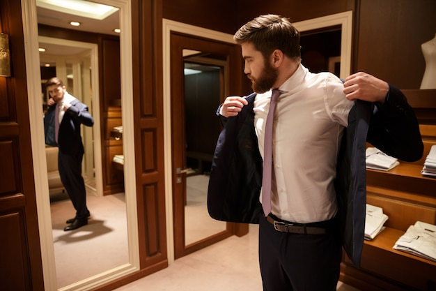 Bearded man putting on his jacket