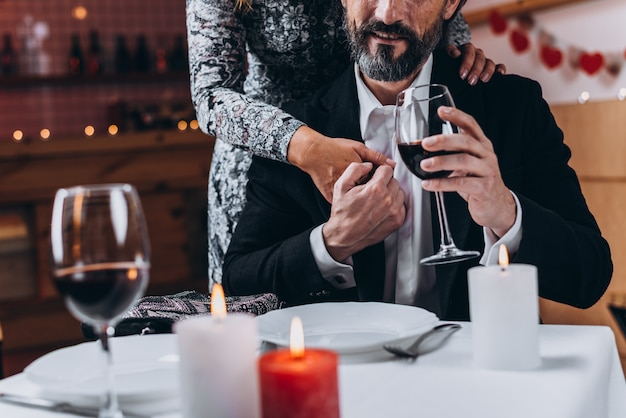Bearded man raises his glass and holds the hand of a woman hugging him