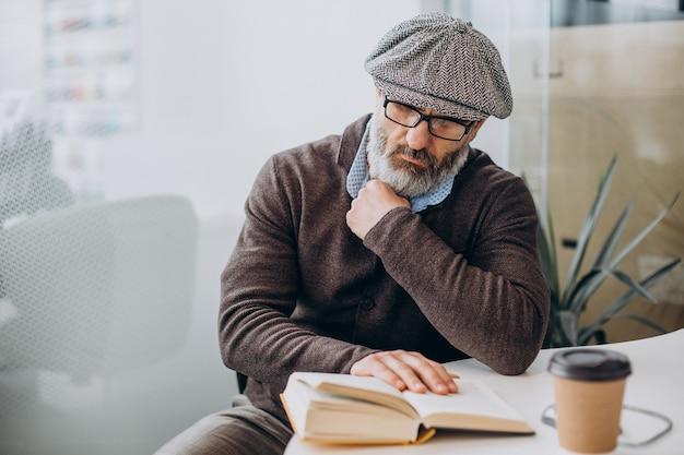 本を読んでテーブルに座っているひげを生やした男