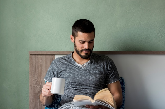 Bearded man reading book and holding cup