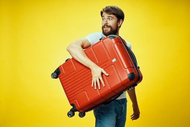 ひげを生やした男の赤いスーツケース黄色の背景の休暇