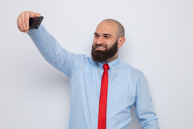 Bearded man in red tie and blue shirt doing selfie using smartphone smiling cheerfully happy and positive
