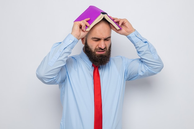 Bearded man in red tie and blue shirt holding book over his head looking tired and annoyed