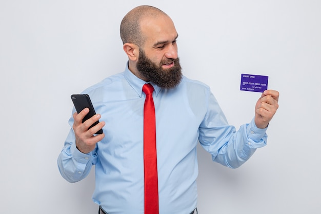 Bearded man in red tie and blue shirt holding smartphone and credit card looking at card happy and pleased smiling cheerfully standing over white background