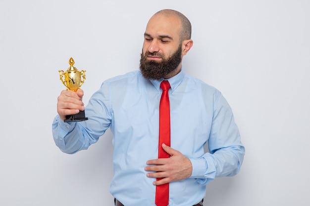 Uomo barbuto in cravatta rossa e camicia blu che tiene in mano un trofeo guardandolo con un sorriso sul viso felice in piedi su sfondo bianco
