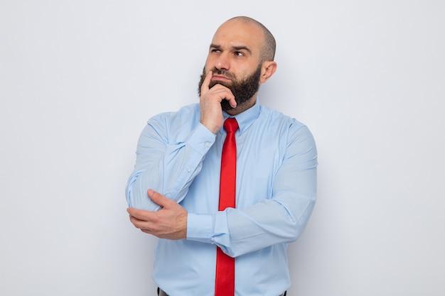 Uomo barbuto in cravatta rossa e camicia blu che guarda da parte con espressione pensosa con la mano sul mento in piedi su sfondo bianco