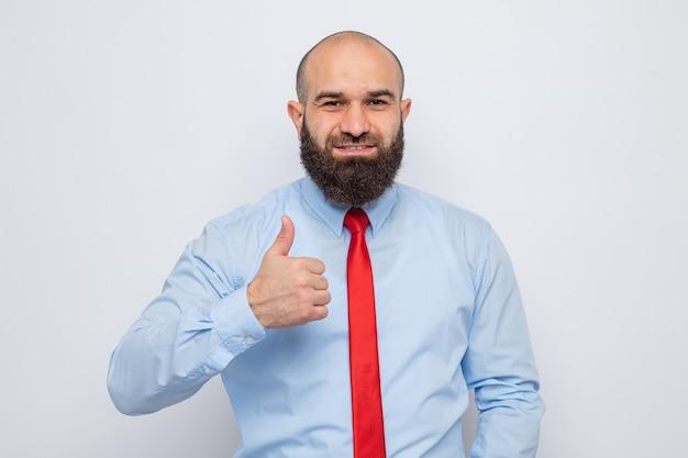 Uomo barbuto in cravatta rossa e camicia blu che sembra sorridente fiducioso che mostra i pollici in su