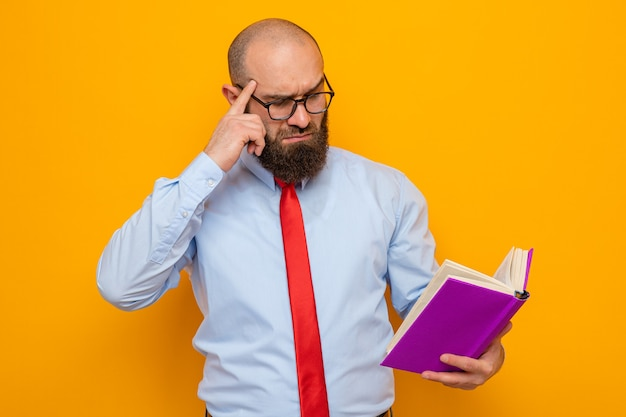 Bearded man in red tie and blue shirt wearing glasses holding book looking at it puzzled thinking