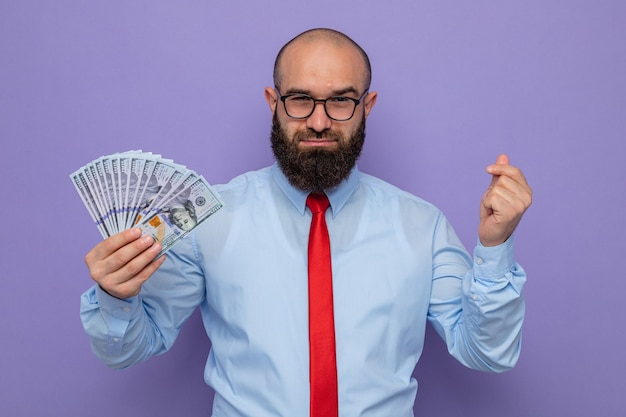 Bearded man in red tie and blue shirt wearing glasses holding cash looking at camera happy and confident smiling making money gesture rubbing fingers standing over purple background
