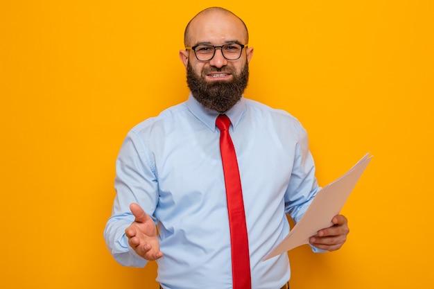 Uomo barbuto in cravatta rossa e camicia blu con gli occhiali in possesso di documenti che cercano di offrire un saluto a mano