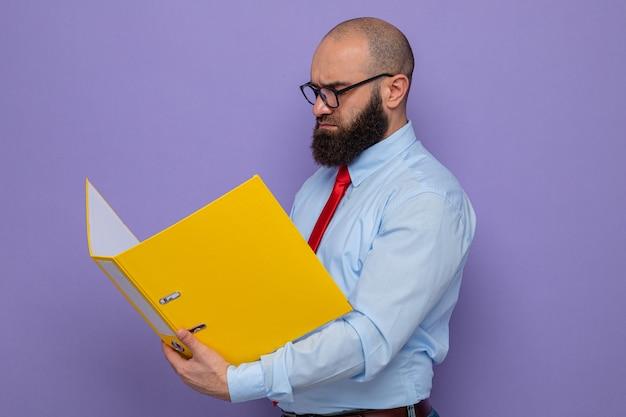Uomo barbuto in cravatta rossa e camicia blu con gli occhiali che tengono la cartella dell'ufficio guardandola con una faccia seria