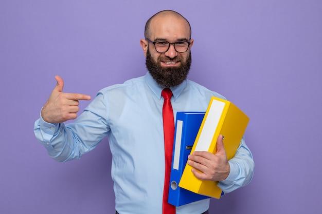 Uomo barbuto in cravatta rossa e camicia blu con gli occhiali che tengono le cartelle dell'ufficio che puntano con il dito indice a guardarli sorridendo allegramente