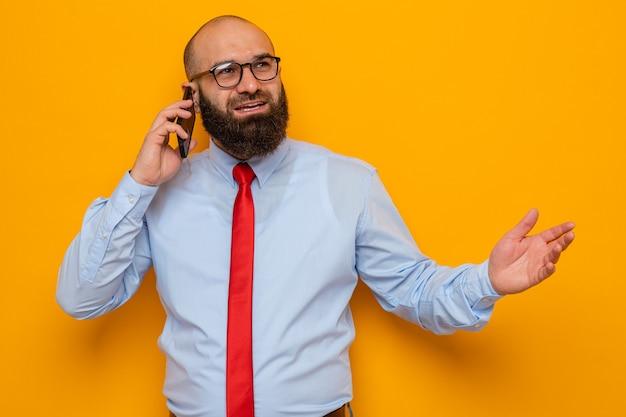 Uomo barbuto in cravatta rossa e camicia blu con gli occhiali che guarda da parte felice e positivo sorride allegramente mentre parla al telefono cellulare