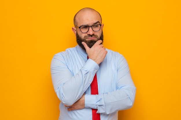 Bearded man in red tie and blue shirt wearing glasses looking aside with hand on his chin with pensive expression thinking