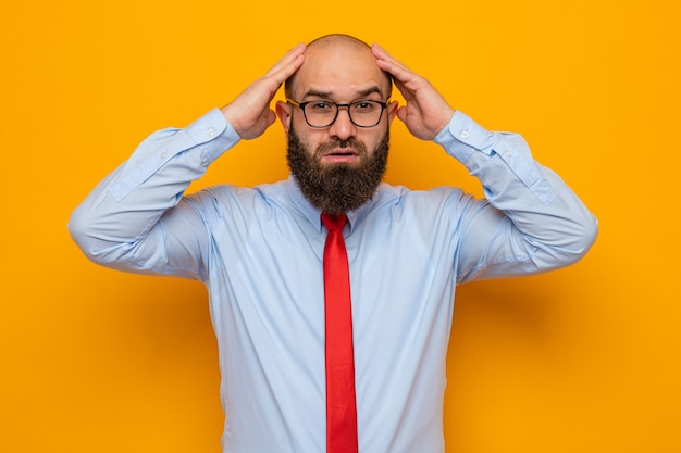 Bearded man in red tie and blue shirt wearing glasses looking at camera confused with hands on his head for mistake standing over orange background