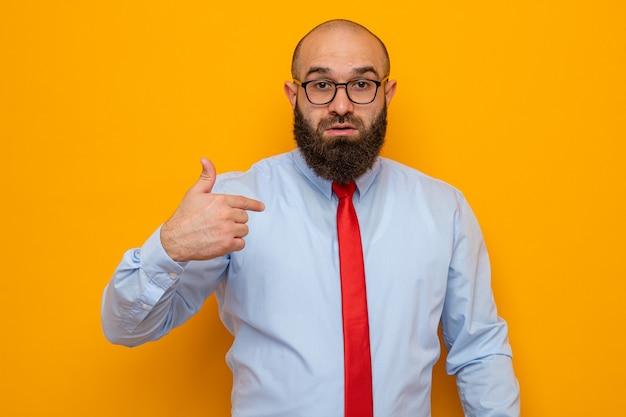 Uomo barbuto in cravatta rossa e camicia blu con gli occhiali guardando la telecamera sorpreso puntando con il dito indice su se stesso in piedi su sfondo arancione