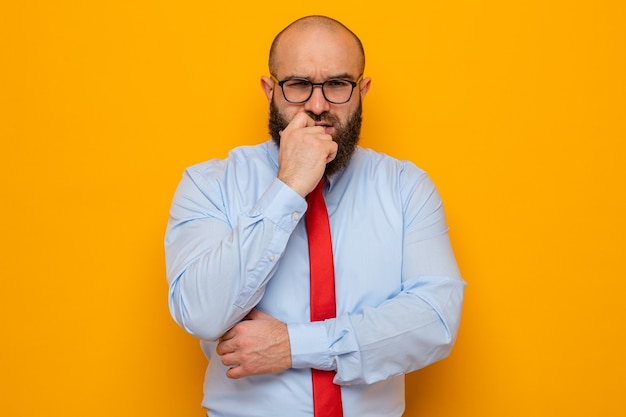 Bearded man in red tie and blue shirt wearing glasses looking at camera with hand on his chin thinking standing over orange background