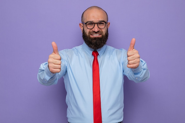 Bearded man in red tie and blue shirt wearing glasses looking happy and positive showing thumbs up