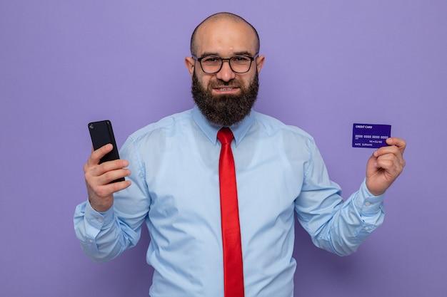 Uomo barbuto in cravatta rossa e camicia blu con gli occhiali smartphone e carta di credito che guarda l'obbiettivo felice e positivo sorridente allegramente in piedi su sfondo viola