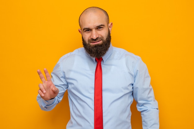 Bearded man in red tie and shirt looking at camera smiling cheerfully showing number two with fingers standing over orange background