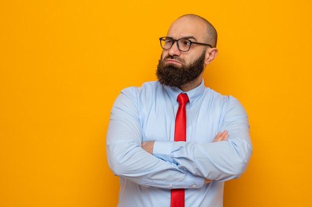 Uomo barbuto in cravatta rossa e camicia con gli occhiali che guarda da parte con le braccia incrociate con espressione scettica