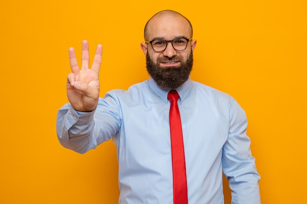Bearded man in red tie and shirt wearing glasses looking at camera smiling confident showing number three with fingers standing over orange background