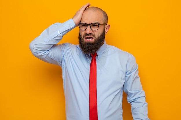Uomo barbuto in cravatta rossa e camicia con gli occhiali che sembra confuso tenendo la mano sulla testa per errore in piedi su sfondo arancione orange