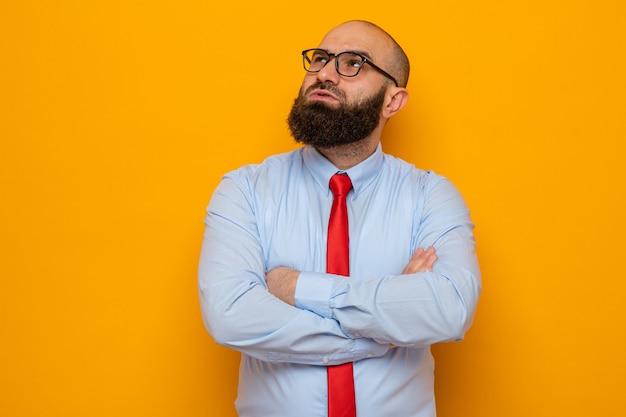 Uomo barbuto in cravatta rossa e camicia con gli occhiali che guarda in alto con espressione pensosa con le braccia incrociate