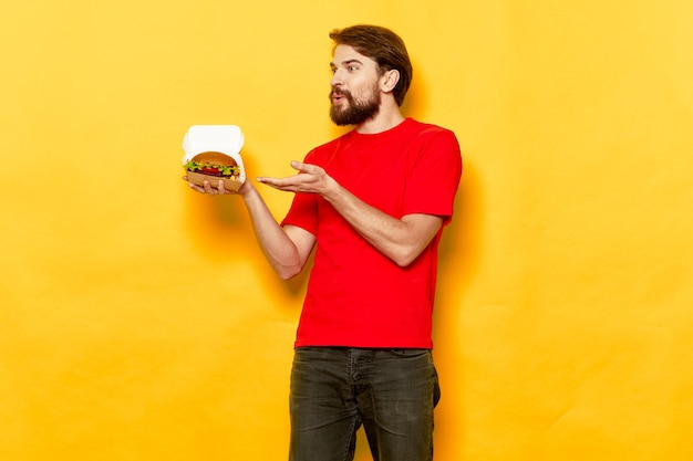 Bearded man in a red tshirt hamburger in the hands of a fast food snack
