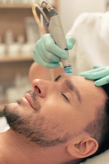 Бородатый мужчина расслабляется с закрытыми глазами, пока профессиональный косметолог ухаживает за кожей лба