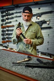 ひげを生やした男が銃店のカウンターで拳銃をリロードします。武器屋のインテリア、弾薬と弾薬の品揃え、銃器の選択、射撃の趣味とライフスタイル、護身術