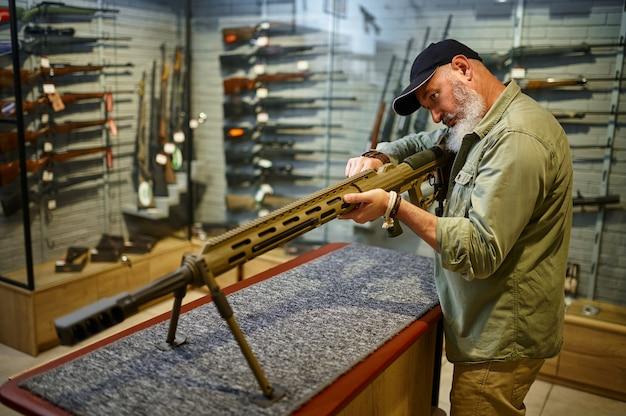 ひげを生やした男が銃の店で強力なライフルをリロードします。武器屋のインテリア、弾薬と弾薬の品揃え、銃の選択、射撃の趣味とライフスタイル、護身術