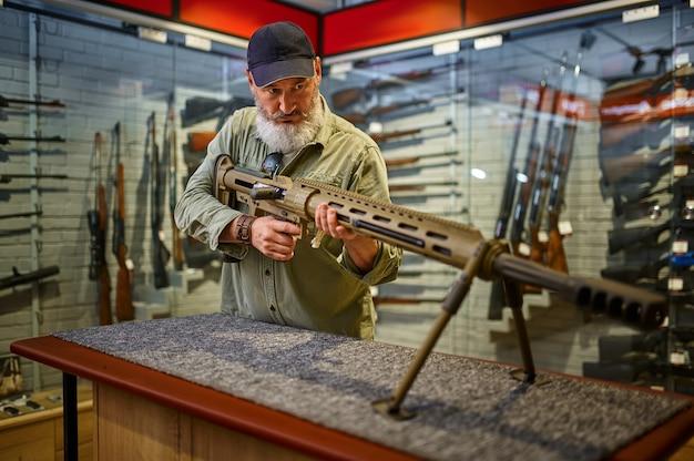 ひげを生やした男が銃の店で強力なライフルをリロード
