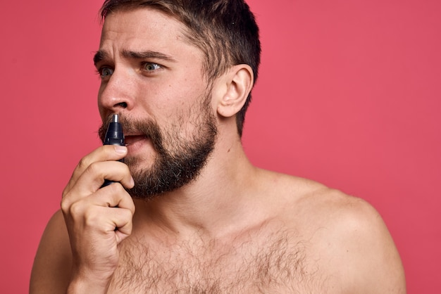 Bearded man removes hair from nose isolated