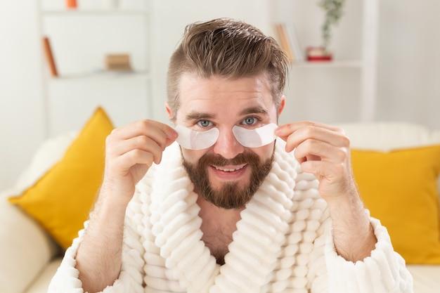 Бородатый мужчина удаляет повязки с глаз на лице. уход за морщинами и лицом в домашних условиях для мужчин.