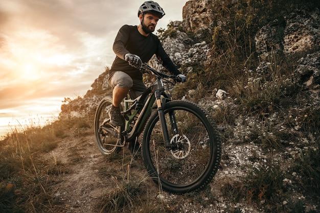 Бородатый мужчина, езда на велосипеде в горах