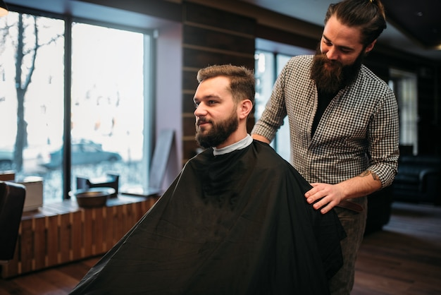 Bearded man in salon cape at the barbershop, barber prepares to cut