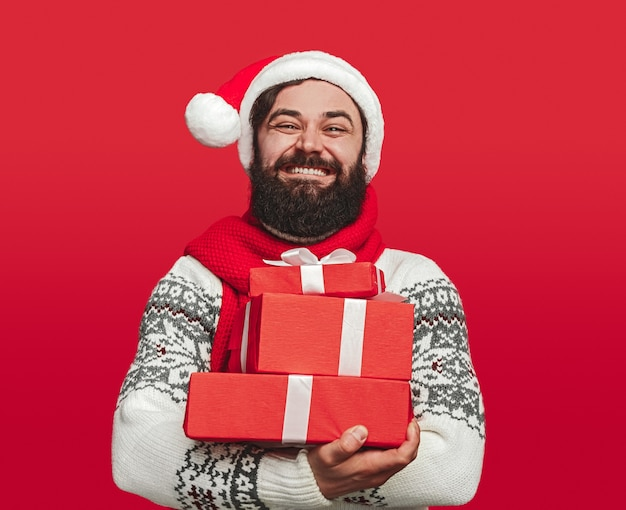 Bearded man in santa hat embracing stack of presents