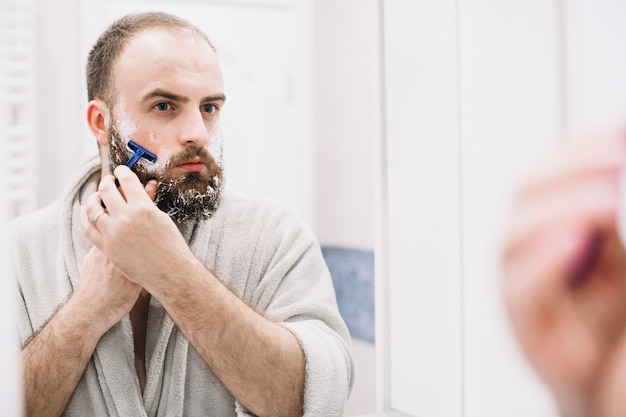 Bearded man shaving in front of mirror