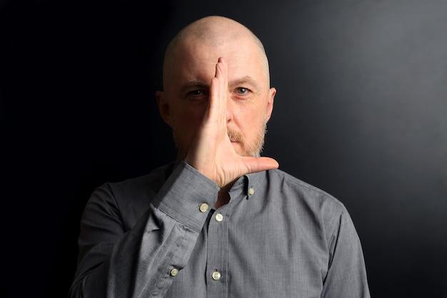 수염 난 남자는 손바닥으로 빛으로부터 얼굴의 절반을가 렸습니다.