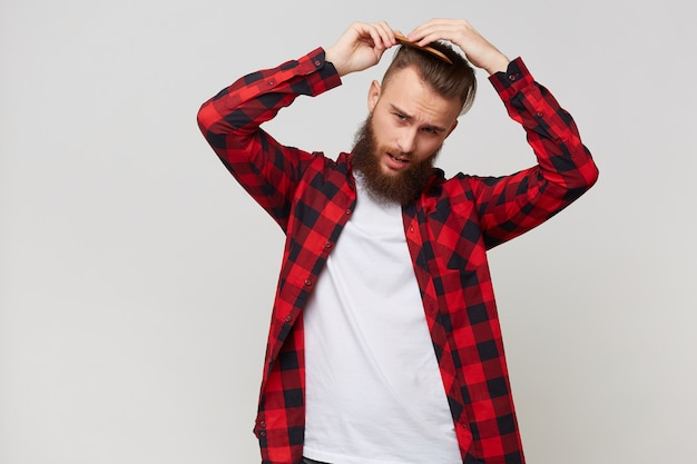 Bearded man in shirt with not very glad facial expression doing modern hairstyle, grooming his hair with comb with discontent isolated over white background