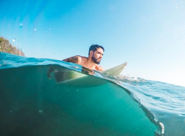 Bearded man in shorts sitting on surfboard in water